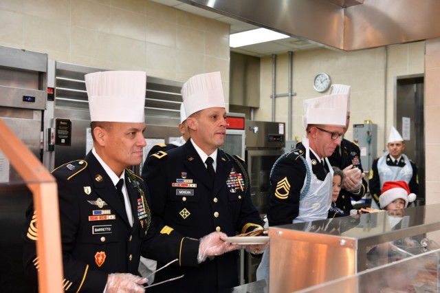 CAMP BONIFAS, Republic of Korea -  Maj. Gen. D. Scott McKean, San Jose, California native, commanding general, 2ID/RUCD and Command Sgt. Maj. Phil K. Barretto, Aiea, Hawaii native, 2ID/RUCD sergeant major serve Thanksgiving meals to Soldiers who are stationed away from home at Bonifas Dining Facility Nov. 22. The command team traveled around the Republic of Korea, ensuring they served meals to as many Warriors as possible, a long-standing military tradition on the holidays where leaders serve their Soldiers to demonstrate appreciation for their hard work and dedication.