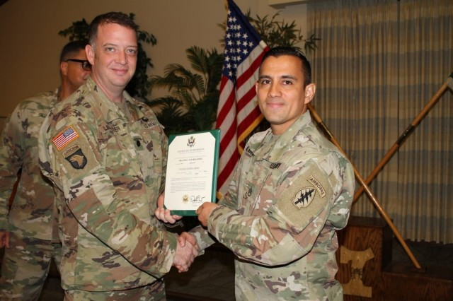 U.S. Army Staff Sgt. Orlando Alvarez, right, a parachute rigger assigned to the Group Support Battalion, 7th Special Forces Group (Airborne), receives an award from Lt. Col. Daniel A. Lancaster, left, Group Support Battalion commander, 7th Special Forces Group (Airborne), at Eglin Air Force Base, Fla.