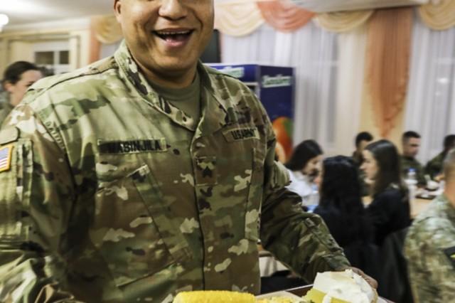 Sgt. Daniel Masinjila of the 278th Armored Cavalry Regiment deployed in Ukraine, gets his Thanksgiving dinner at Yavoriv, Ukraine, Nov. 22.