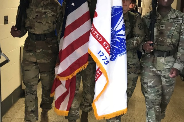 The 20th Chemical, Biological, Radiological, Nuclear, Explosives Command color guard leads the parade at the John Archer School on Nov. 12 to start their American Education Week program and assembly. From left to right, the color guard Soldiers are Spc. Jason Rubio from Belton, Texas; Sgt. William Pridgen from Kinston, North Carolina; Spc. Kayla Riehl from Colorado Springs, Colorado; and Spc. Tedrick Jackson from Fort Worth, Texas. Children waved red, white and blue pompoms as the parade, which included local veterans and a drummer, passed their classrooms.