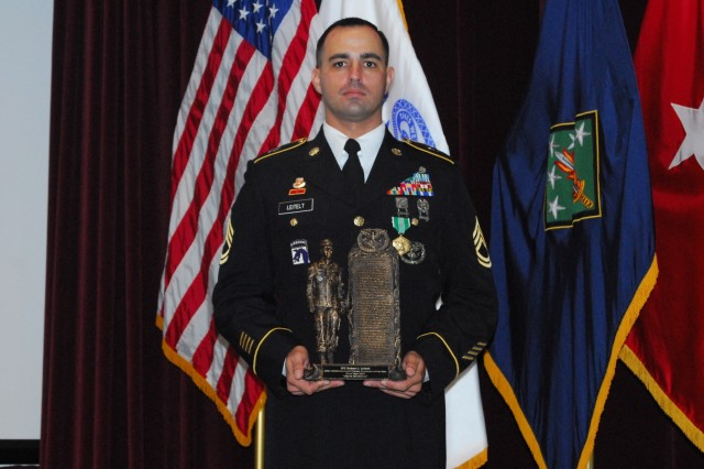 Wearing his new Army Achievement Medal, Sgt. 1st Class Robert Leitelt holds his award as the 2019 career counselor of the year for the 20th Chemical, Biological, Radiological, Nuclear, Explosives (CBRNE) Command at the Nov. 16 ceremony. Leitelt, a Chicago native from the 83rd CBRN Battalion, 48th Chemical Brigade at Fort Stewart, Georgia, was selected for a second year in a row for this prestigious award. He will now represent the command at the career counselor competition for the U.S. Army Forces Command.