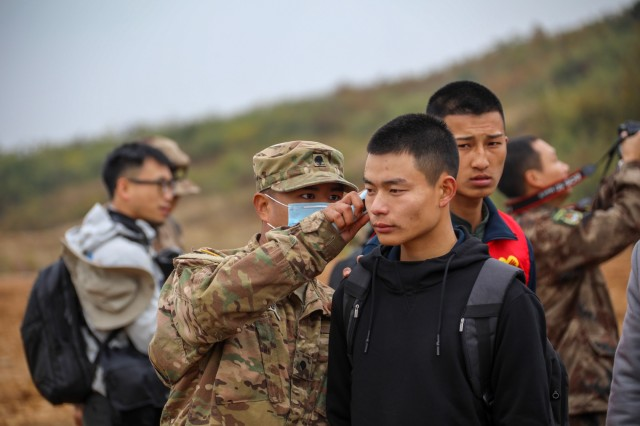 A U.S. Army Soldier checks the temperature of a civilian role player during the practical field exchange of the 2018 Disaster Management Exchange, 13-18 Nov. in Nanjing China. The DME is an annual USARPAC and PLA disaster risk reduction event, which underscores the commitment of both U.S. and the PRC to address Humanitarian Assistance and Disaster Relief challenges across the region. The 2018 DME focused on an international disaster relief scenario following a hypothetical devastating earthquake in a third country.