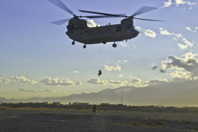 An Airmen rappels from a U.S. Army CH-47 Chinook Helicopter assigned to Company B, 1st Battalion, 171st Aviation Regiment, 101st Combat Aviation Brigade, 101st Airborne Division (Air Assault), Task Force Shadow, during hoist operation training. Utilizing the hoist is provides the military with a method of personnel recovery.