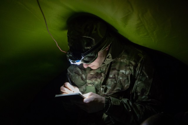 Soldier assigned to Battle Group Poland maps out a nighttime maneuver plan during the Cold Weather Warfare Training event on Nov. 22 in Bemowo Piskie Training Area, Poland. Involving approximately fifty soldiers from the U.K., United States, Romania and Croatia, the exercise covered various skillsets concerning cold weather survival: land navigation, shelter building, nocturnal maneuvers and hypothermia medical care. (Photo by U.S. Army Sgt. Sarah Kirby)