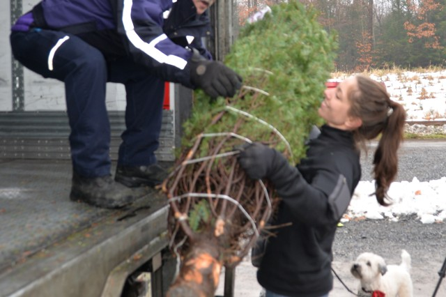 New York Air National Guard Staff Sgt. Shannon Schiller, assigned to the 109th Airlift Wing in Scotia, N.Y., passes a donated Christmas tree to FedEx driver Don Pelletier in trees at Ellms Tree Farm in Ballston Spa, N.Y., November 26, 2018. Nearly 20 volunteers turned out to help load 130 Christmas Trees bound for military families at Fort Bragg, N.C. The effort supported Trees for Troops, a nationwide campaign of the Christmas Spirit Foundation to deliver donated trees to military personnel and their families across the country and around the globe.