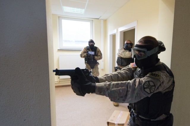 U.S. Army Spc. Scarlett Mitchell, with Chièvres Provost Marshall Office at U.S. Army Garrison Benelux, clears a hallway as her team reacts to a simulated active shooter situation in Caserne Daumerie, Chièvres, Belgium, Dec. 12, 2017. The Soldiers trained for their law enforcement evaluation.