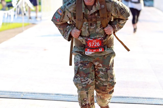 Sgt. 1st Class John Garrett of the Indiana National Guard jogs a portion of the Fort4Fitness marathon, Sept. 29, 2018 in Fort Wayne, Ind.  Garrett participates in road races wearing a 50-pound rucksack with a sign on the back providing the number to a veterans crisis hotline.