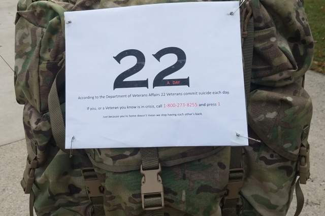 "Sgt. 1st Class John Garrett displays the sign on the back of his rucksack that he wore during the ""Galloping Gobbler"" road race in Fort Wayne, Ind., Nov. 24, 2018.  The sign draws attention to veteran suicides and provides a number to a veterans' crisis hotline."