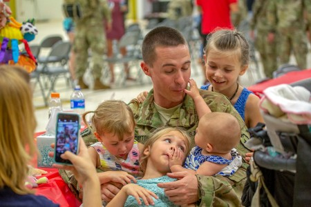 A Soldier with the 25th Aviation Regiment embraces his family at a ceremony honoring the troops prior to their deployment at Wheeler Army Airfield, Hawaii, Jun. 5, 2018. The 3rd Battalion, 25th Aviation Regiment will support Operation Freedom's Sentinel and Operation Resolute Support in Central Command's area of responsibility.