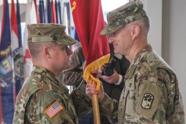 Ansbach, GERMANY - Col. Richard A. Wholey, Jr. (left), commander of the 678h Air Defense Artillery Brigade, passes the battalion colors to Lt. Col. Todd Daniels, commander of the 5th Battalion, 4th Air Defense Artillery Regiment, during the 5-4 ADA activation and assumption of command ceremony on Shipton Kaserne, Germany Noveber 28. Daniels is the first commander of the newly activated brigade after 20 years of lying dormant. (Photo by Capt. Robert Durr, 10th AAMDC PAO)