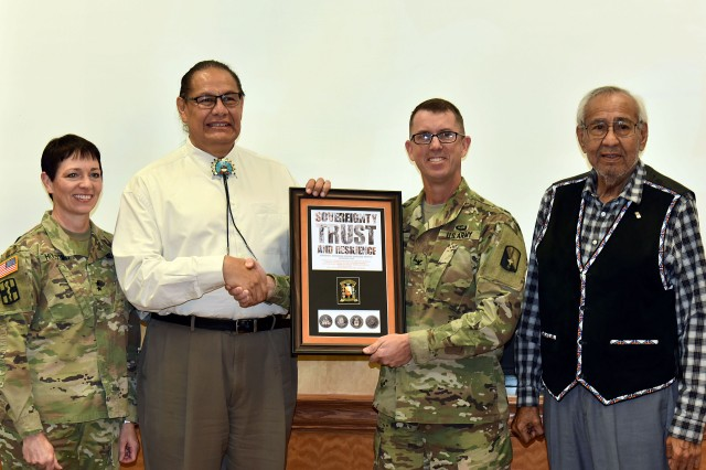 Senior installation commander Maj. Gen. Barbara R. Holcomb, left, and Col. Paul Howard, center right, commander of the 21st Signal Brigade, present Dennis W. Zotigh, center left, keynote speaker, with a plaque during a Native American Heritage Month observance program at Fort Detrick Nov. 26, 2018. Zotigh currently works for the Smithsonian Institution's National Museum of the American Indian. He is a Kiowa, San Juan Pueblo and Santee Dakota Indian.