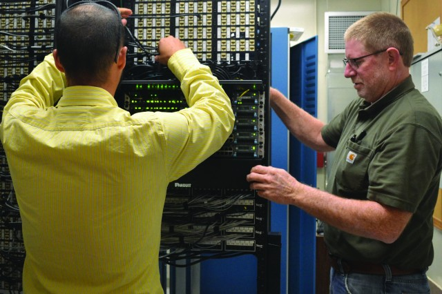Josh Mizell and Ray Harbison, both IT specialists with Pine Bluff Arsenal's Directorate of Information Management, check out the various communication lines on new network switches that were recently installed on the installation.