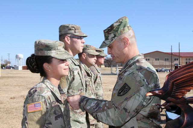Sgt. Makayla Highler, 2-18th FA,  receives the Army Commendation Medal from Command Sgt. Maj. John Foley, Fires Center of Excellence and Fort Sill CSM, Nov. 26, 2018, as she was recognized as the FCoE Best Warrior NCO of the Year.