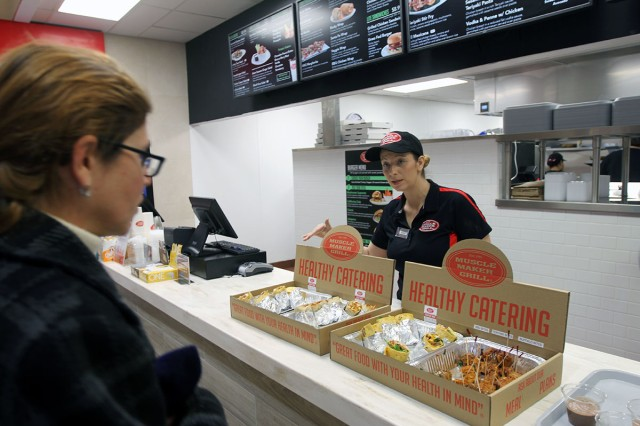 Muscle Maker Grill manager Wendy Leach offers free samples to a patron during the grill's grand opening Nov. 21, 2018, at Fort Sill.  It was the third Muscle Maker Grill to open at an Army post.
