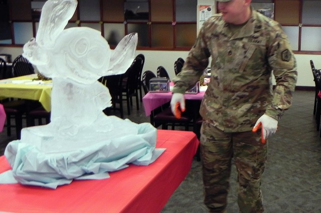 Food service specialist Sgt. 1st Class Joshua Perry of Army Human Resources Command at Fort Knox, Ky., inspects a tropical-themed ice sculpture prior to a Thanksgiving meal hosted Nov. 21, 2018, at Guns and Rockets Dining Facility on post.