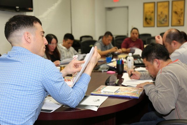 Maj. Gregory Costello, assigned to U.S. Army Japan Staff Judge Advocate, left, teaches military spouses, local national employees and members of Japan Ground Self-Defense English during an Army Community Service's English as a Second Language class held Nov. 14, 2018, on Camp Zama, Japan.