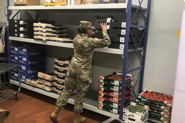 Spc. Niya Kennedy, Food Inspector Specialist from Baumholder checks lunch meat items sold at a grocery store on post.