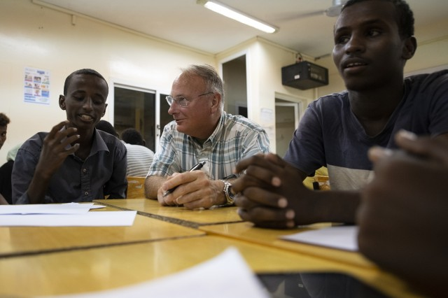 "U.S. Army Capt. Michael Volk, a civil affairs officer, 403rd Civil Affairs Battalion, Combined Joint Task Force-Horn of Africa, Camp Lemonnier, Djibouti, works with students during the first-ever English Language Discussion Group (EDG) in the neighborhood of Balbala, Djibouti, Nov. 29, 2018. The EDG serves as a ""language laboratory"" in which students develop practical linguistic and rhetorical skills through relationship building and information exchange. (U.S. Air Force photo by Tech. Sgt. Shawn Nickel)"