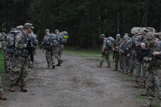 Competitors in the 2018 I Corps Best Warrior Competition prepare for a road march of an undisclosed distance during the 2nd day of the competition on May 15, 2018, at Joint Base Lewis-McChord. All competitors were required to carry over 35 pounds in their ruck sack and complete the course as quickly as possible. (U.S. Army photo by Sgt. Kyle Larsen)