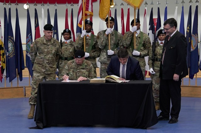 "U.S. Army Col. Seth Knazovich, left, commander of the 41st Field Artillery Brigade, and Edgar Knobloch, right, mayor of Grafenwoehr, Germany, sign a partnership agreement during the unit's activation ceremony in Grafenwoehr, Nov. 30, 2018. The 41st Field Artillery Bde. ""Railgunners"" is the new unit activating in Grafenwoehr, Germany under the training readiness authority of 7th Army Training Command and will provide long-range precision fires capabilities for U.S. Army Europe. (U.S. Army photo by U.S. Spc. Emily Houdershieldt)"
