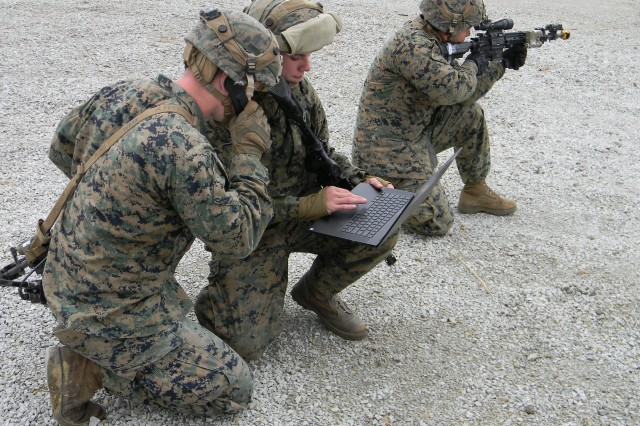 Marines operate a swarm of drone via laptop in an urban environment at Muscatatuck Urban Training Center, Indiana, in November. (Courtesy photo by Tollie Strode Jr., Maneuver Battle Lab)