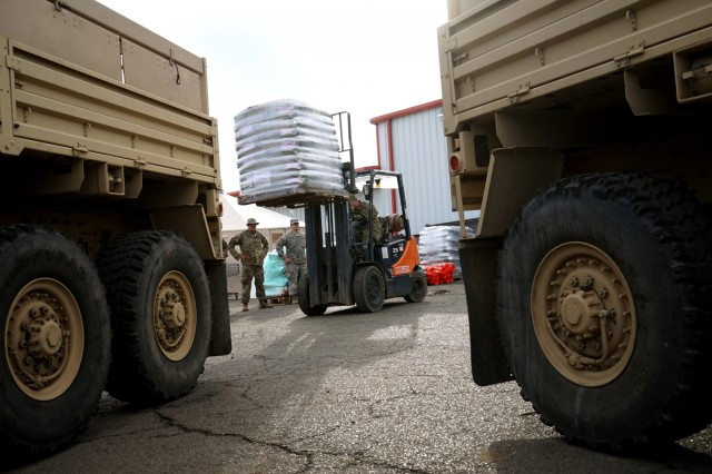 Soldiers from the California Army National Guard's 2632nd Transportation Company use a forklift to load pallets of animal feed into their trucks at a warehouse in Oroville, California, Nov. 26, 2018. The Transportation Company was brought in to carry critical supplies to area residents impacted by the deadly Camp Fire.