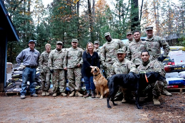 Tina Rickert and her dogs pose with Derek Milsaps, USDA Assistant Director for Northern California, and Soldiers from the California Army National Guard's 2632nd Transportation Company at her home in Magalia, California, Nov. 26, 2018. Rickert, an Air Force veteran, lives just outside the evacuation zone and volunteered her property as a distribution center for critical supplies needed by residents impacted by the deadly Camp Fire.