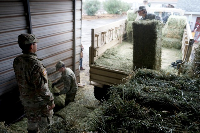 Soldiers from the California Army National Guard's 2632nd Transportation Company unload hay at a ranch in Paradise, California, Nov. 28, 2018. The 2632nd transported critical supplies to area residents who were impacted by the deadly Camp Fire.