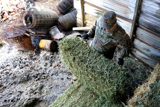 A Soldier from the California Army National Guard's 2632nd Transportation Company moves hay through piles of ash at a ranch in Paradise, California, Nov. 28, 2018. The 2632nd transported critical supplies to area residents who were impacted by the deadly Camp Fire.