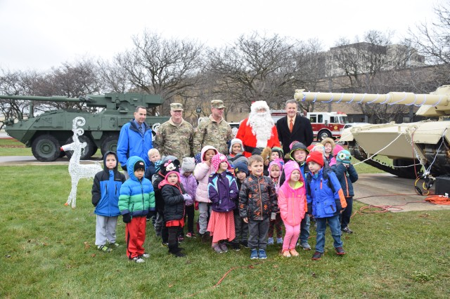Garrison Manager Joseph Moscone with TACOM Command Sgt. Maj. Ian Griffin, TACOM Commander Maj. Gen. Daniel Mitchell, Santa Claus and Dave Sullivan from People Driven Credit Union along with the children from the Child Development Center pose with the Abrams tank.