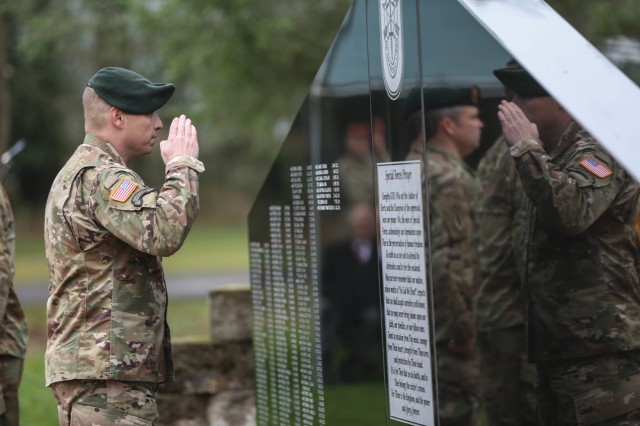 JOINT BASE LEWIS-MCCHORD, Washington- The senior enlisted advisor to the commander of the Headquarters and Headquarters Company, 1st Special Forces Group (Airborne), salutes the names of the fallen 1st SFG (A) Soldiers, Spc. Jeremy Allen and Sgt. 1st Class Reymund Transfiguracion, on the memorial wall at 1st SFG (A) headquarters, Dec 3.  The ceremony, held at the 1st SFG (A) headquarters, commemorates the deactivation of the First Special Service Force in Menton, France on Dec. 5, 1944 and honors those Special Forces Soldiers who have given the ultimate sacrifice.  (U.S. Army photo by Sgt. Ian Ives)