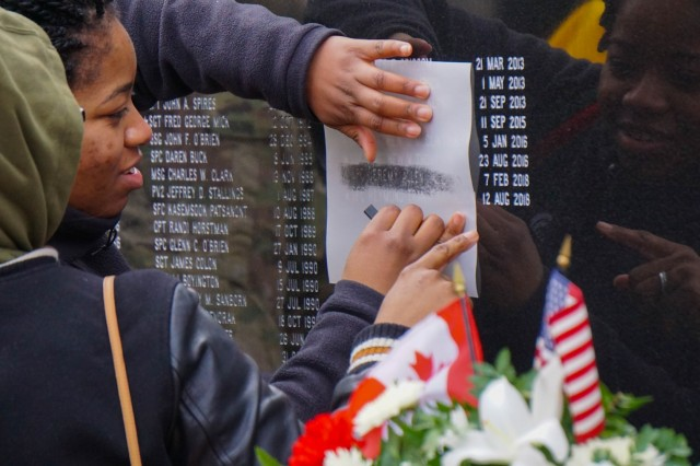 JOINT BASE LEWIS-MCCHORD, Washington- Family members take an etching of Spc. Jeremy Allen's name, a fallen Soldier with 1st Special Forces Group (Airborne), at the 1st SFG (A) memorial wall following the Menton Week memorial ceremony at 1st SFG (A) headquarters, Dec. 3.  The ceremony, held at the 1st SFG (A) headquarters, commemorates the deactivation of the First Special Service Force in Menton, France on Dec. 5, 1944 and honors those Special Forces Soldiers who have given the ultimate sacrifice.  (U.S. Army photo by Sgt. 1st Class Christopher Harper)