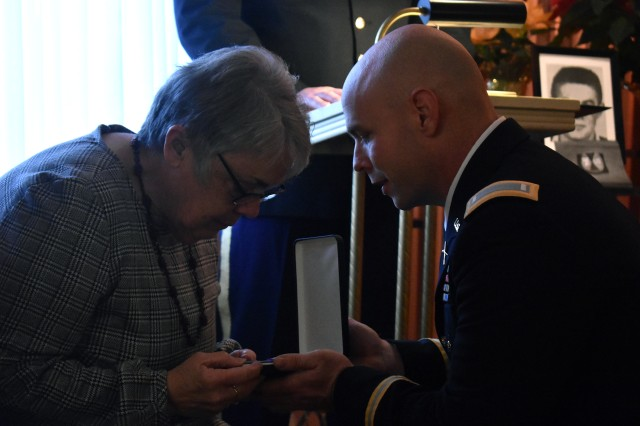 U.S. Army 1st. Lt. John O'Donnell, attached to the 10th Mountain Division, presents Tamaris Dolton, a niece of Pfc. John Martin with a posthumous Purple Heart for Martin, Schuylerville, N.Y., Dec. 2, 2018. The family received the medal for the sacrifice made by Martin, who went missing in action 68 years ago, in the Korean War.
