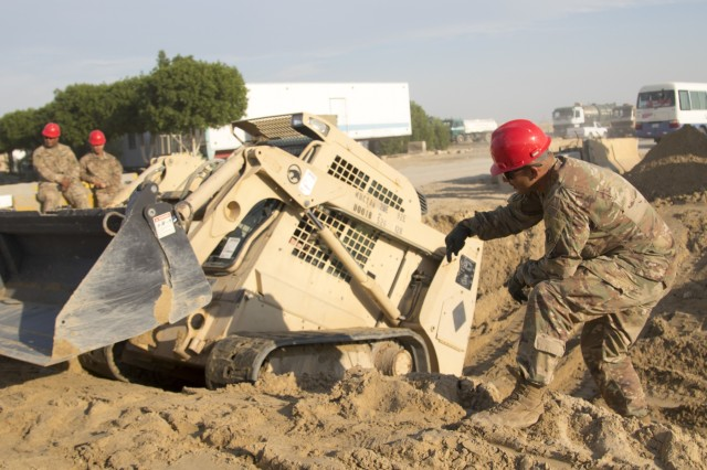 U.S. Army Sgt. Alejandro Jimenez, right, a squad leader with the 526th Engineer Construction Company, 92nd Engineer Battalion, 28th Engineer Brigade, directs U.S. Army Pvt. Sean Ginn, an operator with the 526th ECC, as he smooths out the slope of a trapezoidal ditch with a skid-steer at Camp Arifjan, Kuwait, Nov. 28, 2018. Kuwait has experienced unusually high amounts of rainfall in the past month, and the improvements made to this drainage ditch will help maintain living and operational conditions.