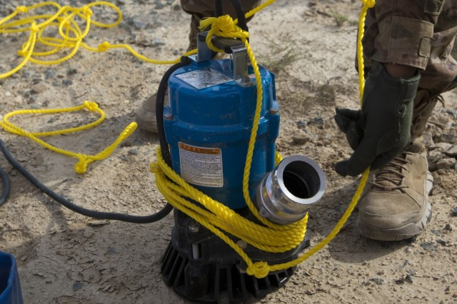 U.S. Army Pfc. Donnesha Streetman, a multi-systems transmission maintainer and operator with U.S. Army Network Enterprise Center-Kuwait, prepares a pump to remove water from an access service point at Camp Buehring, Kuwait, Dec. 1, 2018. Keeping communication lines operational during extreme weather events is an essential task to ensure our personnel remain capable to accomplish their mission.