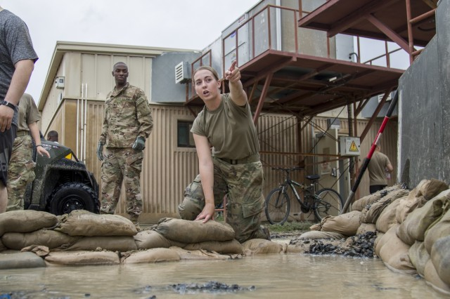 A Soldier directs others where to place sandbags in order to divert flood waters after a rainstorm at Camp Arifjan, Kuwait, November 15, 2018. Soldiers from multiple units joined together to respond to the flooding which had impacted their living quarters.
