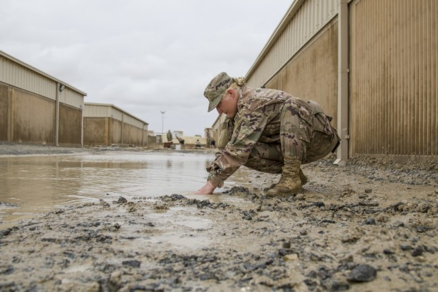 Spc. Nisreen Isbell, a chemical, biological, radiological, and nuclear (CBRN) specialist with the 637th Chemical Company digs a trench with her hands to divert flood waters after a rainstorm at Camp Arifjan, Kuwait, November 11, 2018.The flooding came after an unusually heavy rainstorm hit the area, which has already experienced significant rain this month.