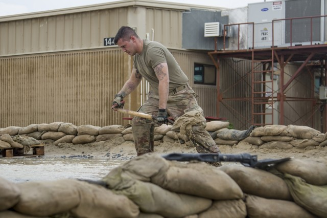 U.S. Army Sgt. Andrew Garden, a wheeled vehicle mechanic assigned to the 949th Veterinary Services Detachment, 8th Medical Brigade, carries a shovelful of sand while reinforcing barriers built to divert flood waters at Camp Arifjan, Kuwait, November 15, 2018. Soldiers from multiple units joined together to respond to the flooding which had impacted their living quarters.