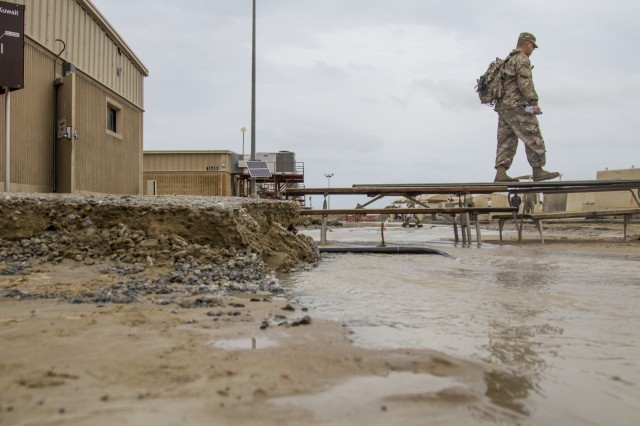 A Soldier walks across a makeshift bridge of picnic tables to avoid  flood waters at Camp Arifjan, Kuwait, November 15, 2018.  The flooding came after an unusually heavy rainstorm hit the area, which has already experienced significant rain this month.
