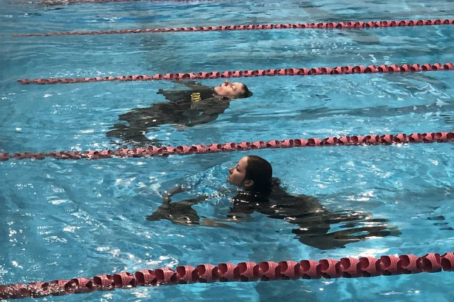 Eastern Washington University (EWU) ROTC Cadets Jameson Palmer (top) and Samantha Knight (bottom) tread water as they remove their uniform at the end of the 100m swim event at the German Armed Forces Proficiency Badge Competition, hosted by EWU ROTC from 17-18 November, 2108.