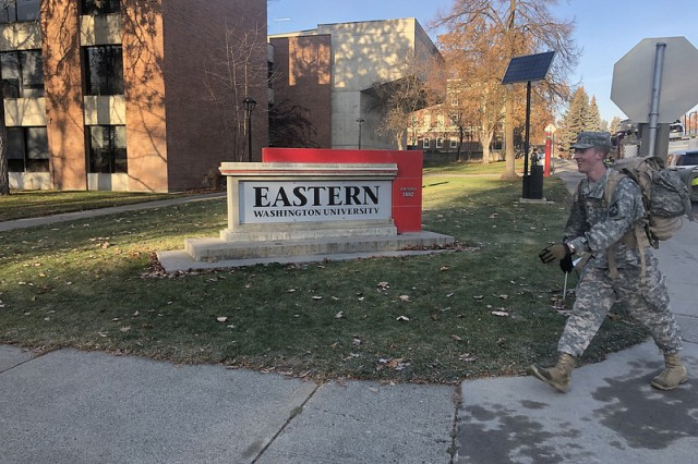 Eastern Washington University (EWU) ROTC Cadet Matthew Jeffs ruck marches by one of the entrance signs to EWU. The ruck was the final event at the German Armed Forces Proficiency Badge Competition, hosted by Eastern Washington University ROTC from 17-18 November, 2108.