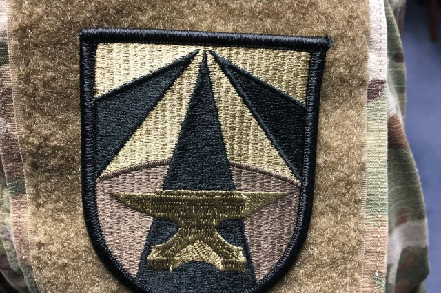 Shoulder sleeve insignia for Army Futures Command. With a golden anvil as its main symbol, the shoulder patch and distinctive unit insignia are a nod to former Gen. Dwight D. Eisenhower's personal coat of arms that used a blue-colored anvil.
