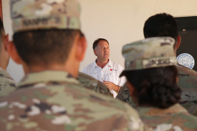 Randy Neeman, the deputy director for the American Red Cross response to Super Typhoon Yutu recovery operations talks to U.S. Army Soldiers with the 9th Mission Support Command, U.S. Army Reserve, currently assigned to Joint Task Group-Saipan, Task Force-West, about their accomplishments in support of recovery operations at the Francisco C. Ada International Airport in Saipan, Commonwealth of the Northern Mariana Islands, Nov. 29, 2018. After Super Typhoon Yutu hit the islands of Saipan and Tinian Oct. 24, several federal agencies immediately began a coordinated disaster response effort, including the Federal Emergency Management Agency, Department of Defense and local government, to help the people of these islands recover. DOD forces used in the initial typhoon response have begun redeploying at the direction of FEMA, based on the needs of the local government.