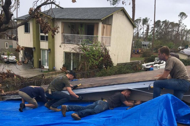 Soldiers and Sailors assigned to the Naval Diving and Salvage Training Center in Panama City Florida help repair a roof in October 2018.