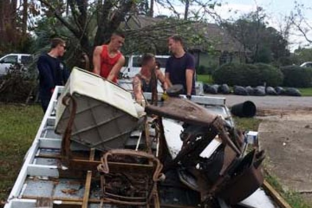 Soldiers assigned to the Naval Diving and Salvage Training Center in Panama City, Florida, help move furniture from a damaged home.