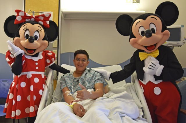 Manuel Anduha (center) receives a special visit by Mickey and friends from the Disney Aulani Resort while receiving care at the Tripler Army Medical Center Pediatric Inpatient Ward, Dec. 4.
