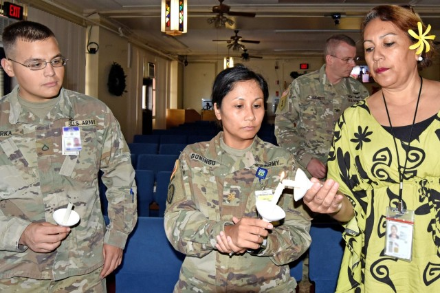 Pfc. Brandon Torka, medic (left), Maj. Carmina Domingo, neurologist, (center), and Polilua Tuita, medical support assistant, (right), light eulogy candles during a hospital memorial service and candlelight vigil to honor President George H.W. Bush, at the Tripler chapel, Dec. 5.