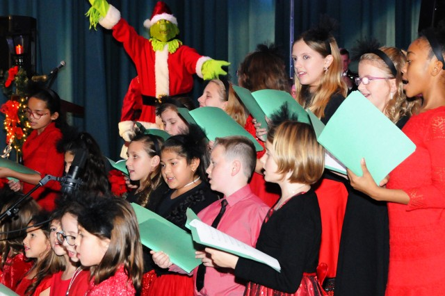Fort Rucker Elementary School students sing at the concert as the Grinch poses in the background.