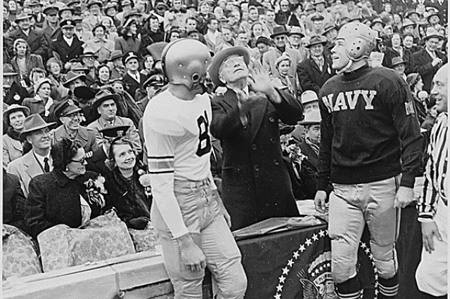 President Harry S. Truman tosses a coin in the air before the annual Army-Navy football game in Philadelphia, Dec. 2, 1950, as the captains of the Army and Navy teams watch on.