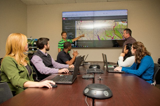 Jimmie Elliott, hydraulic engineer at the U.S. Army Corps of Engineers Vicksburg District, addresses members of the Modeling, Mapping, and Consequences Production Center (MMC). In the background is the trafficability dashboard produced by the MMC.